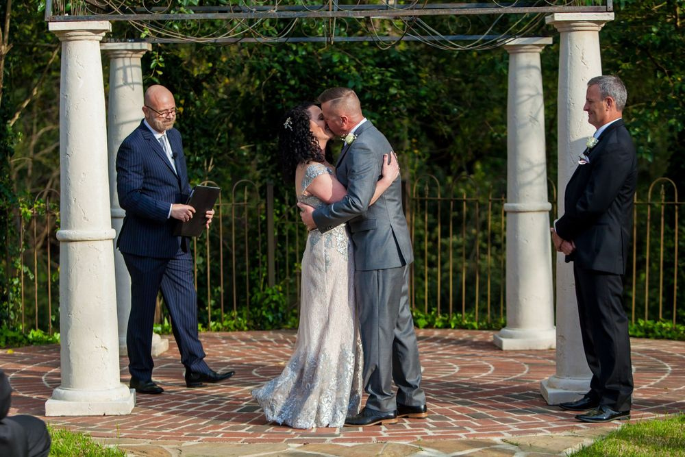 Bride and groom have their first kiss during their wedding ceremony at Senate's End in Columbia, SC