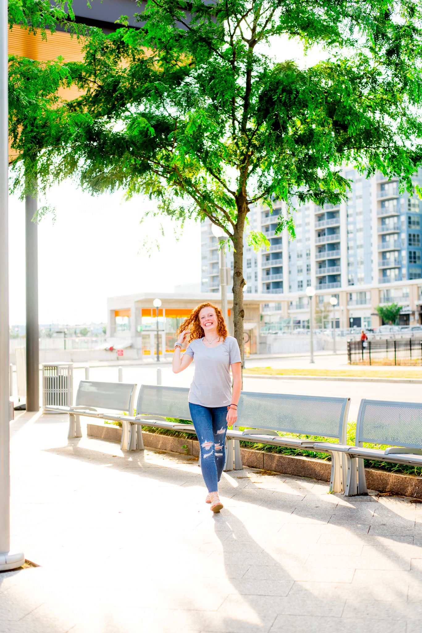 redhead girl in jeans and and grey shirt walking by tree at Smale Riverfront Park Downtown Cincinnati