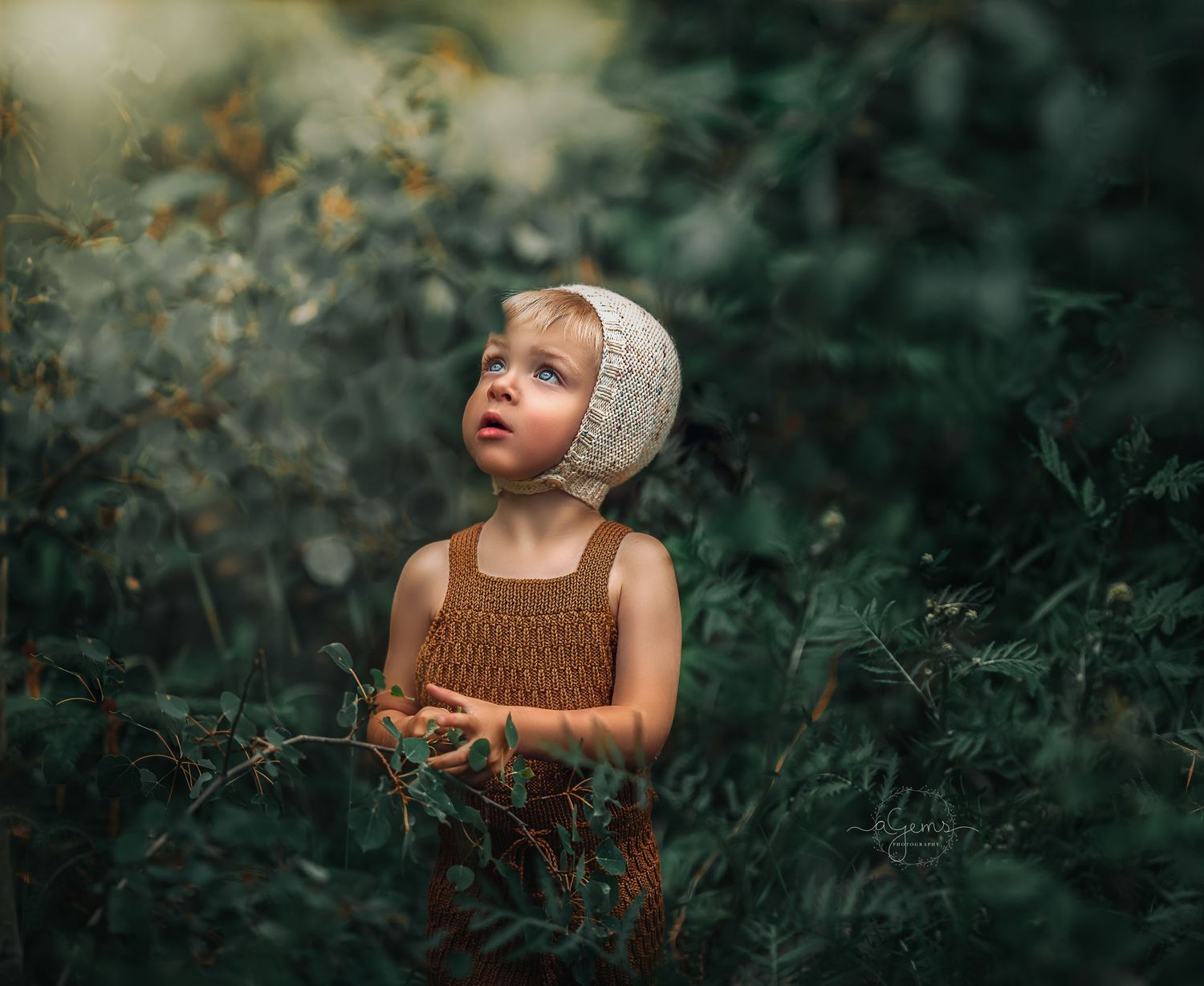 Young child in knit clothing and adorable hand knit bonnet looks at foliage in outdoor green forest session