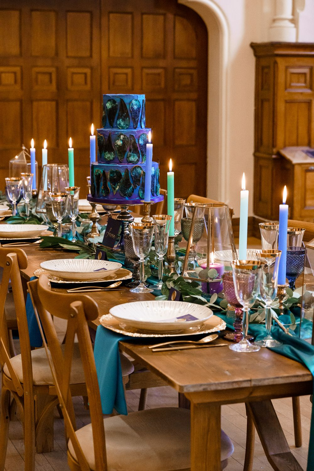 Peacock wedding theme table layout with coloured candles and teal table runner.