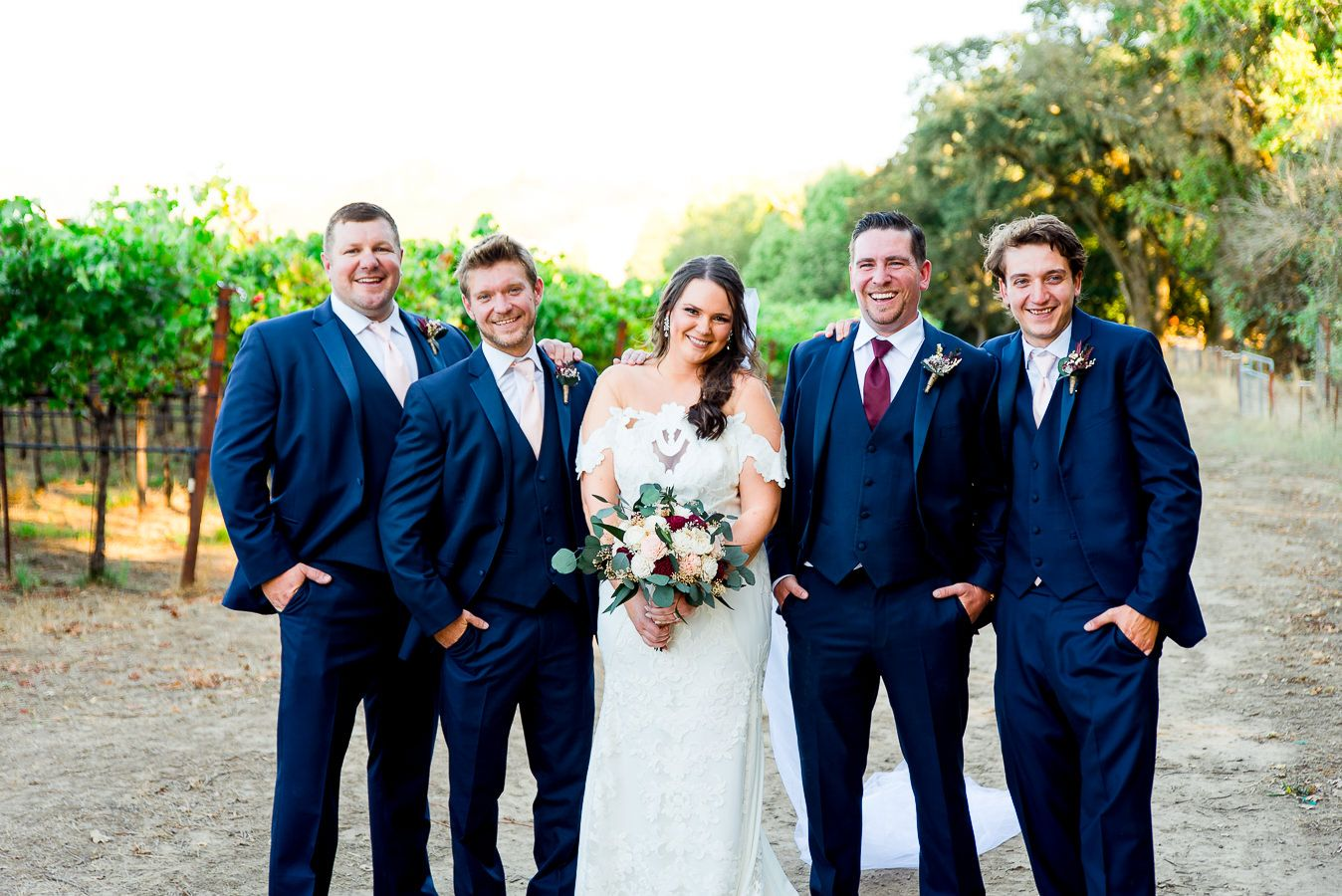 groomsmen in navy suits surround bride on dirt path at Pennyroyal Farm