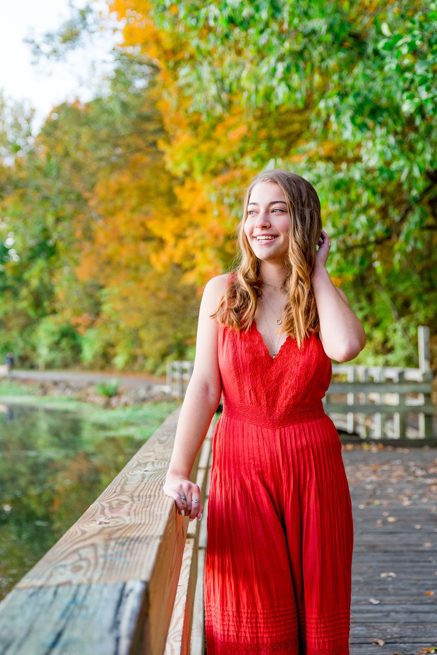 young girl in bright orange jumpsuit standing on a bridge with fall foliage for senior pictures in Chicago