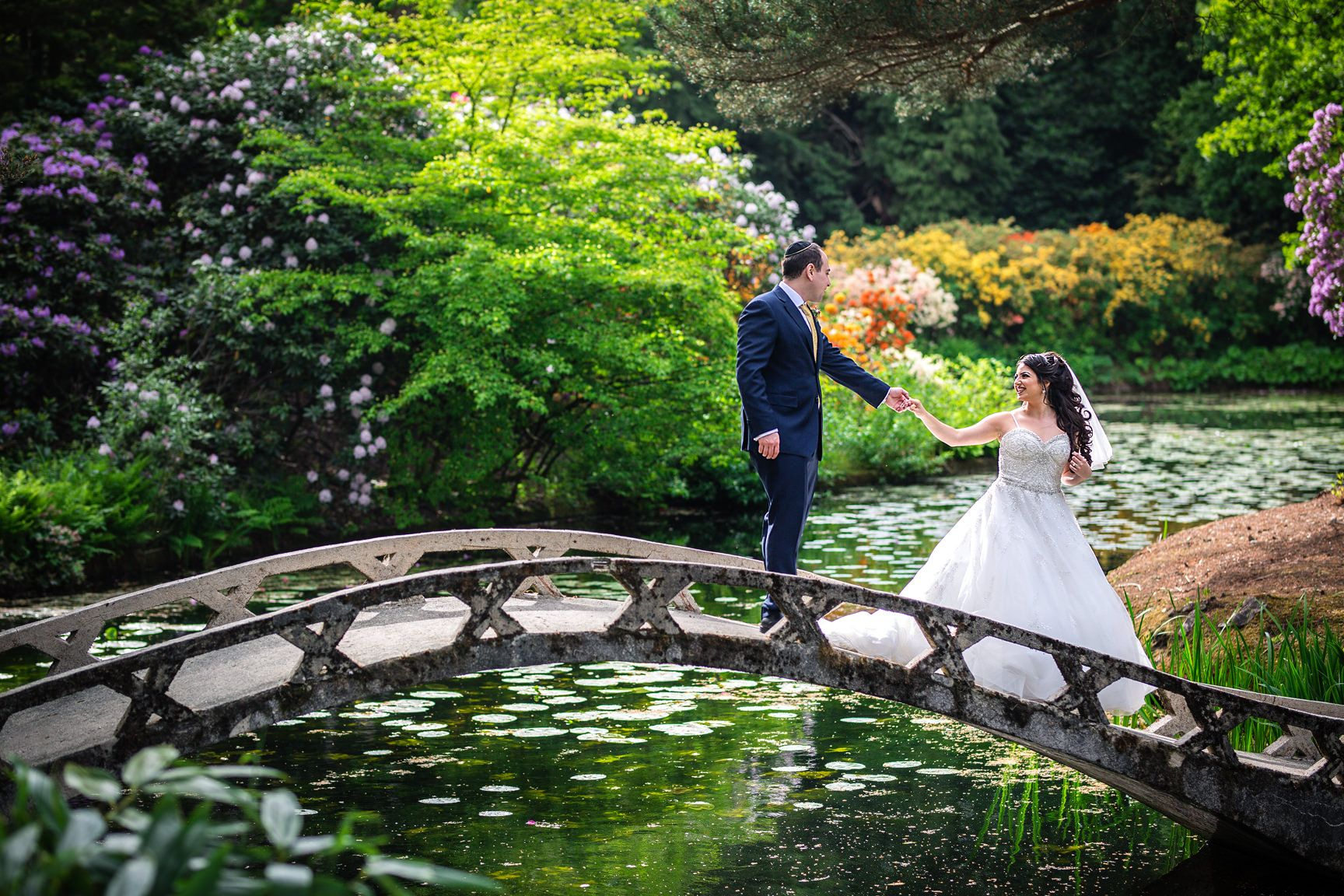 Manchester Jewish wedding photographer captures the bride and groom on a bridge at their Tatton Park wedding in Summer