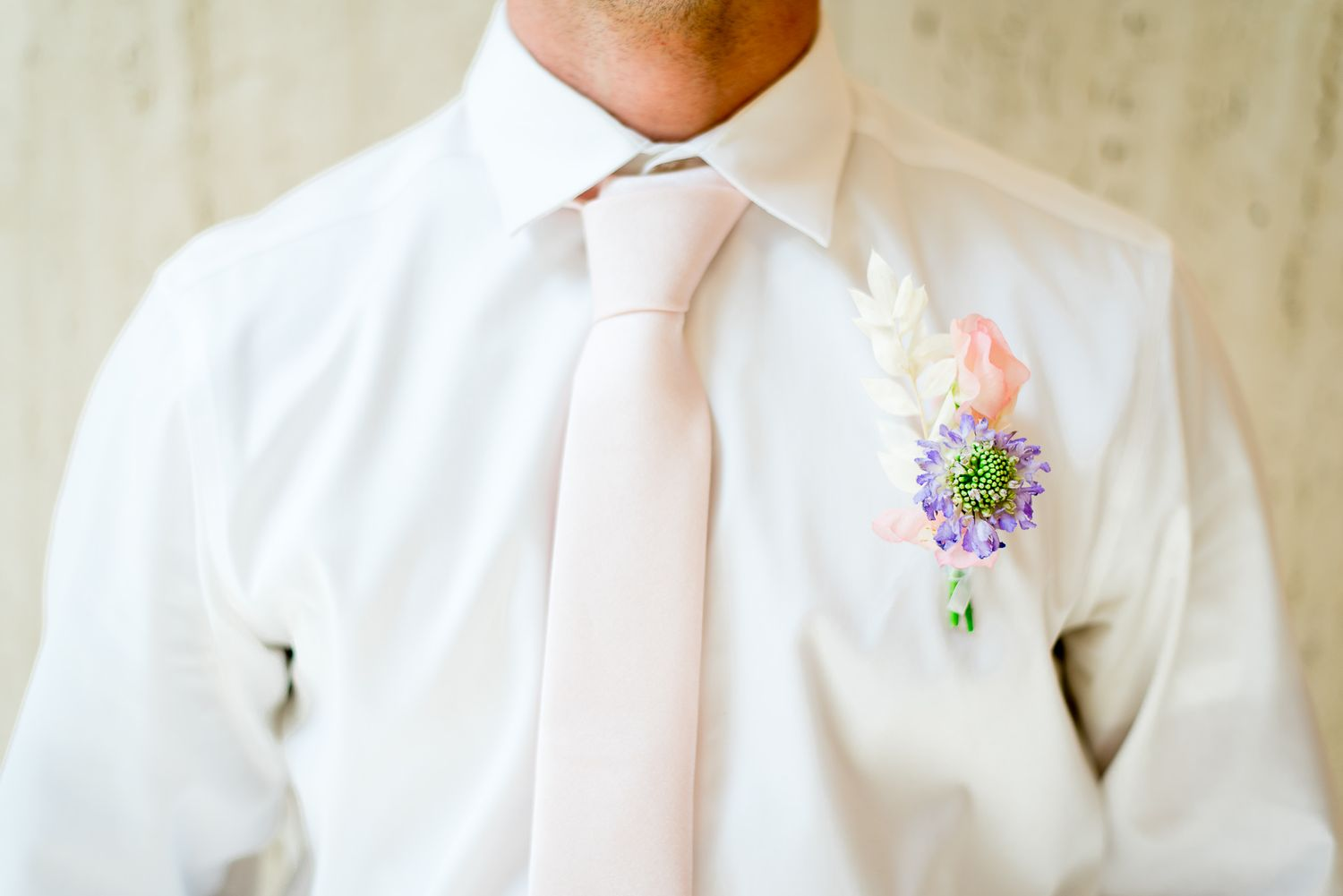 groom wearing white shirt, pink tie, pink and purple boutonniere in front of marble wall at The Center Cincinnati spring