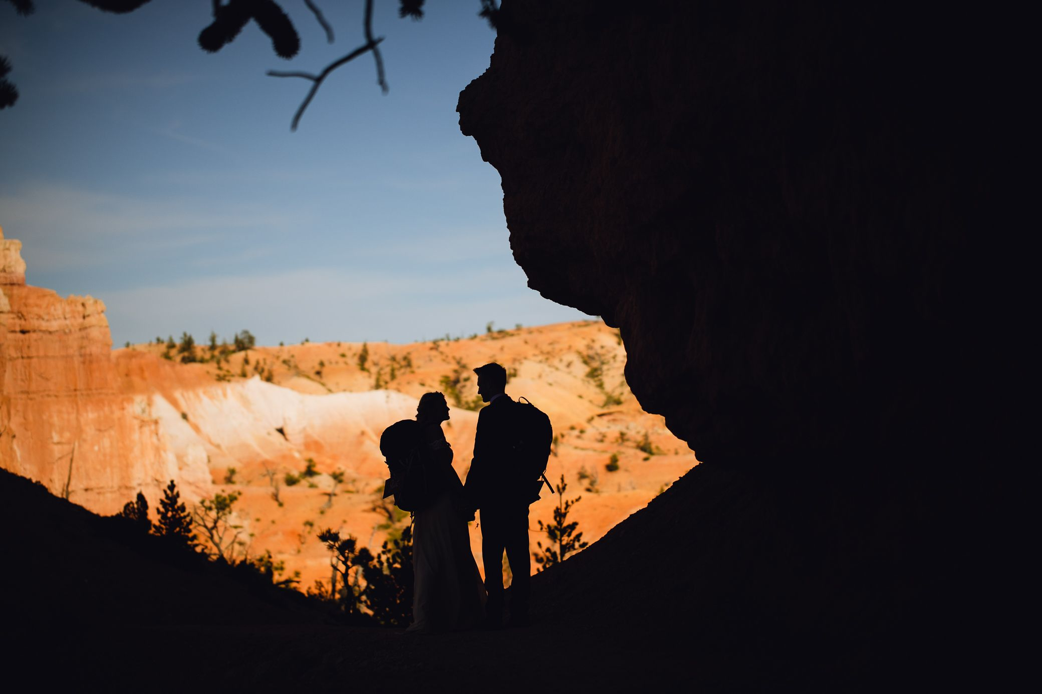 Couple silhouetted with backpacks on at Bryce Canyon National Park.