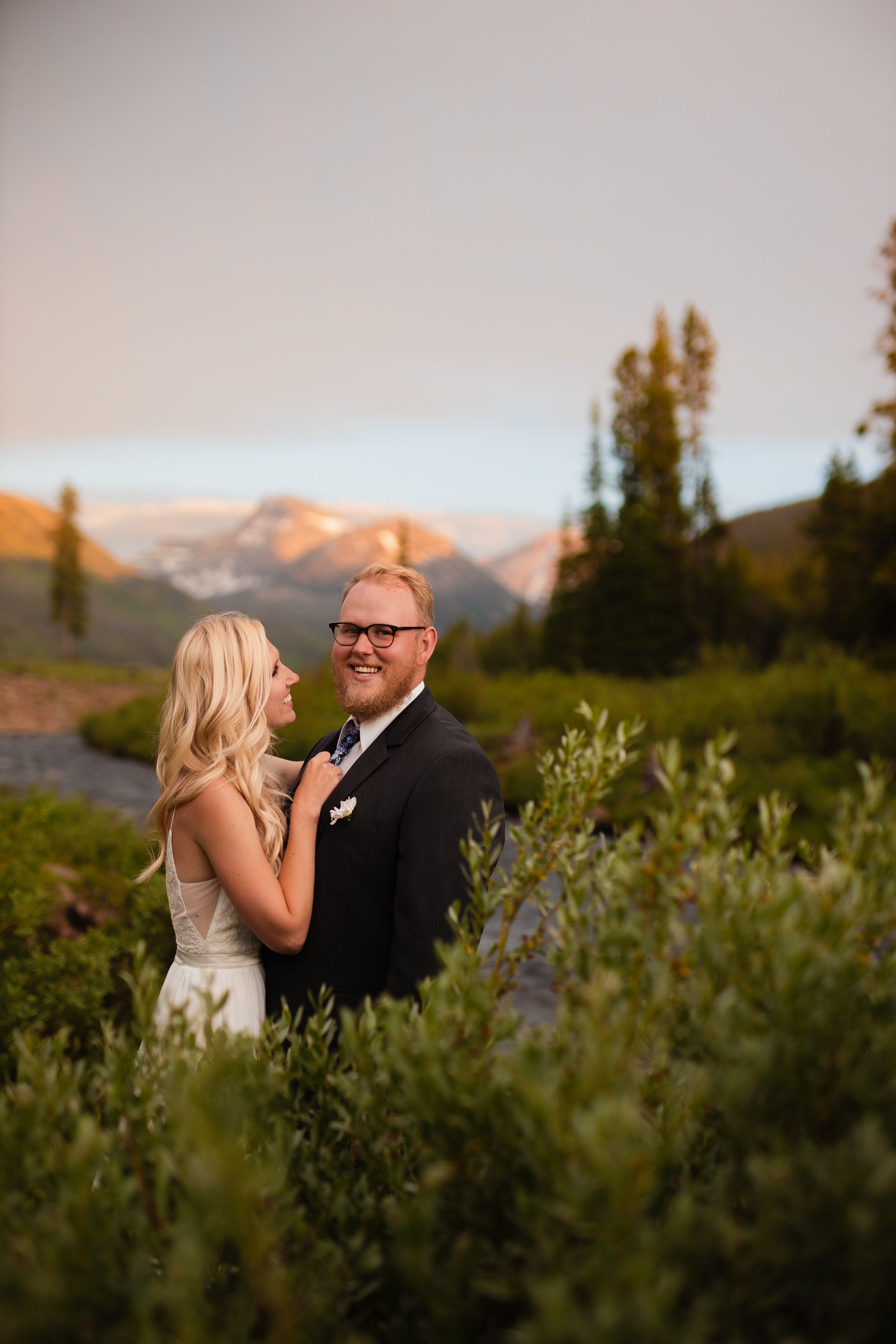 Cute couple in a meadow with mountain peaks, trees, and a river in the background.