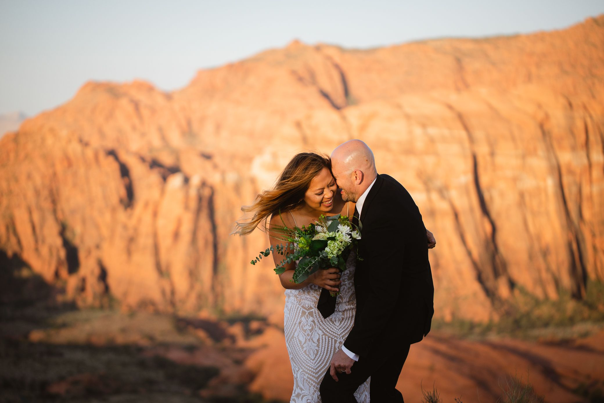 Couple laughing on their wedding day at sunrise in Snow Canyon State Park.