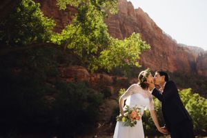 Couple kissing at Zion National Park by a red canyon wall.