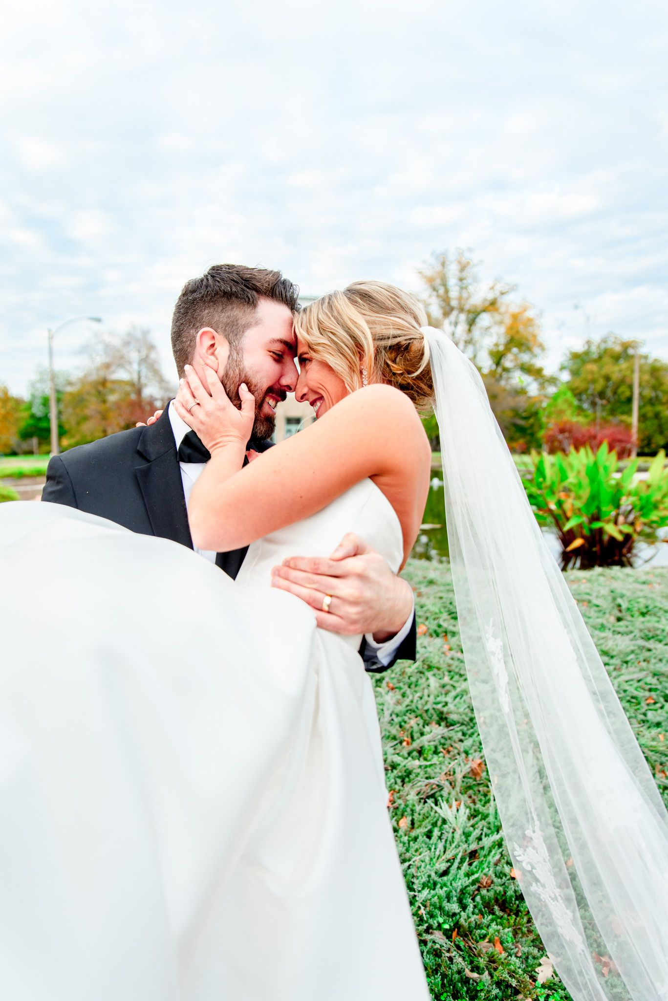groom carrying bride in his arms and smiling at each other at the Jewel Box in Forest Park, STL