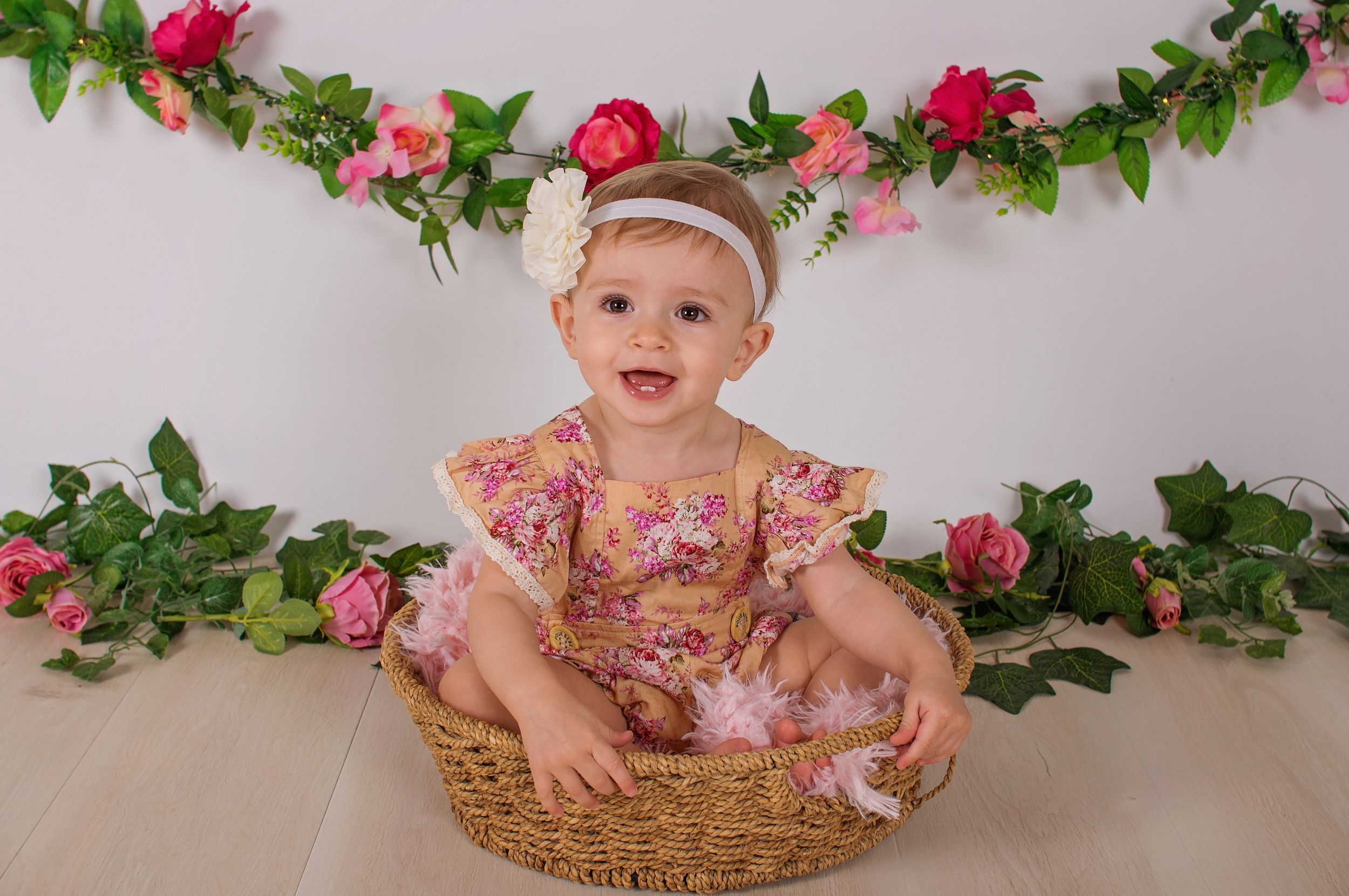 baby girl sitting in basket smiling surrounded by flowers