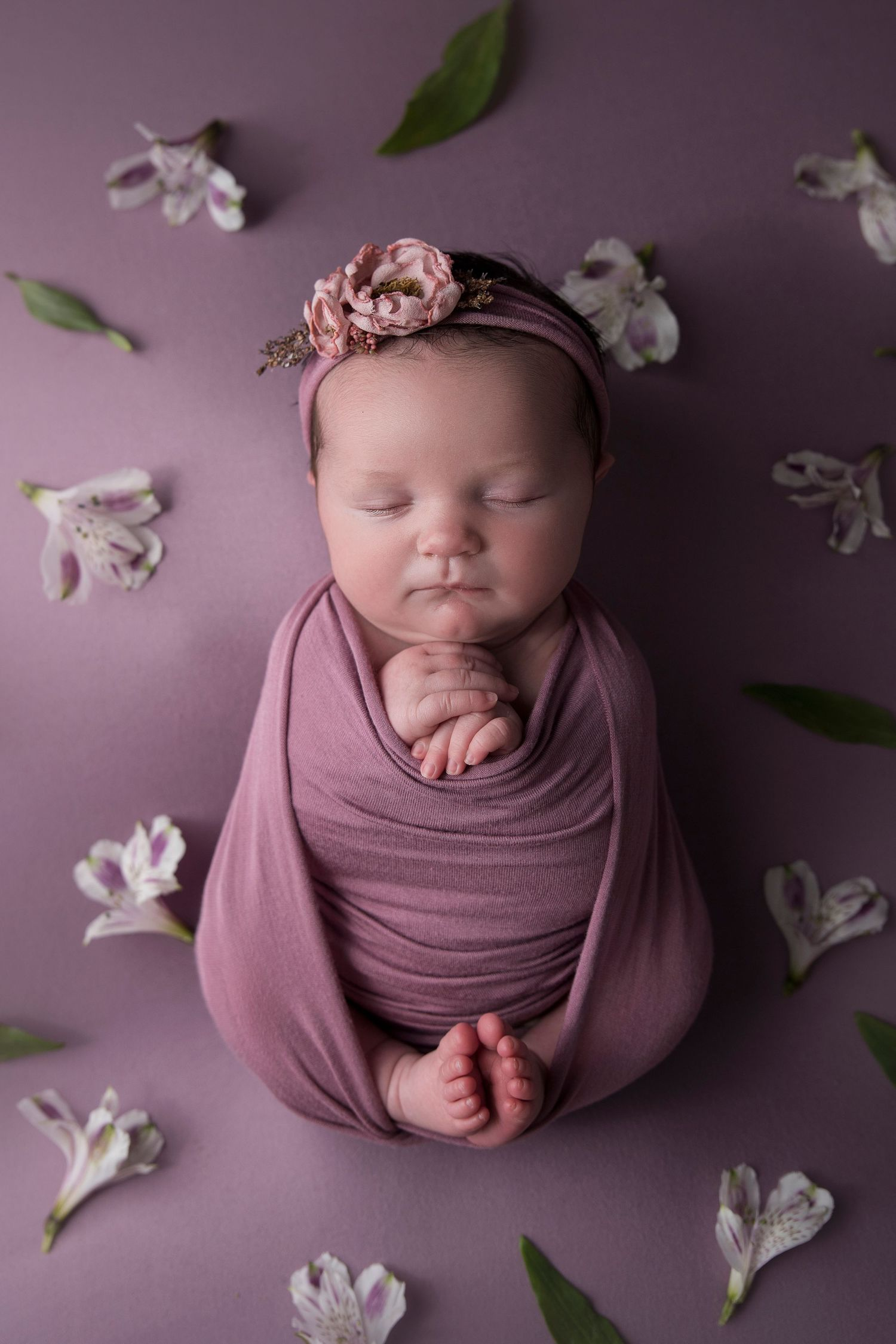 baby girl wrapped in purple with flowers