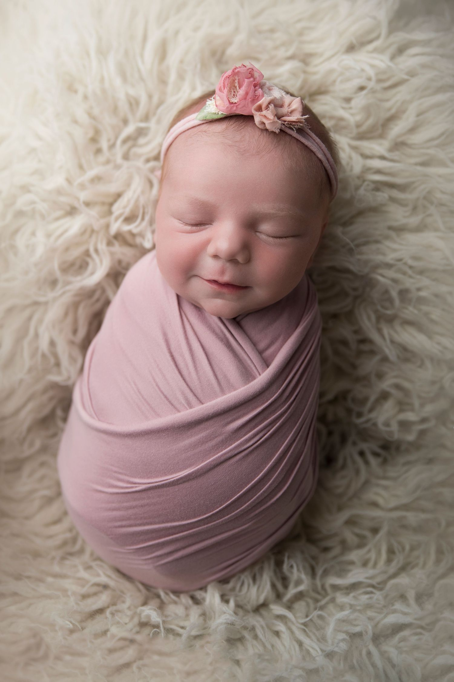 baby girl wrapped in pink on flokati