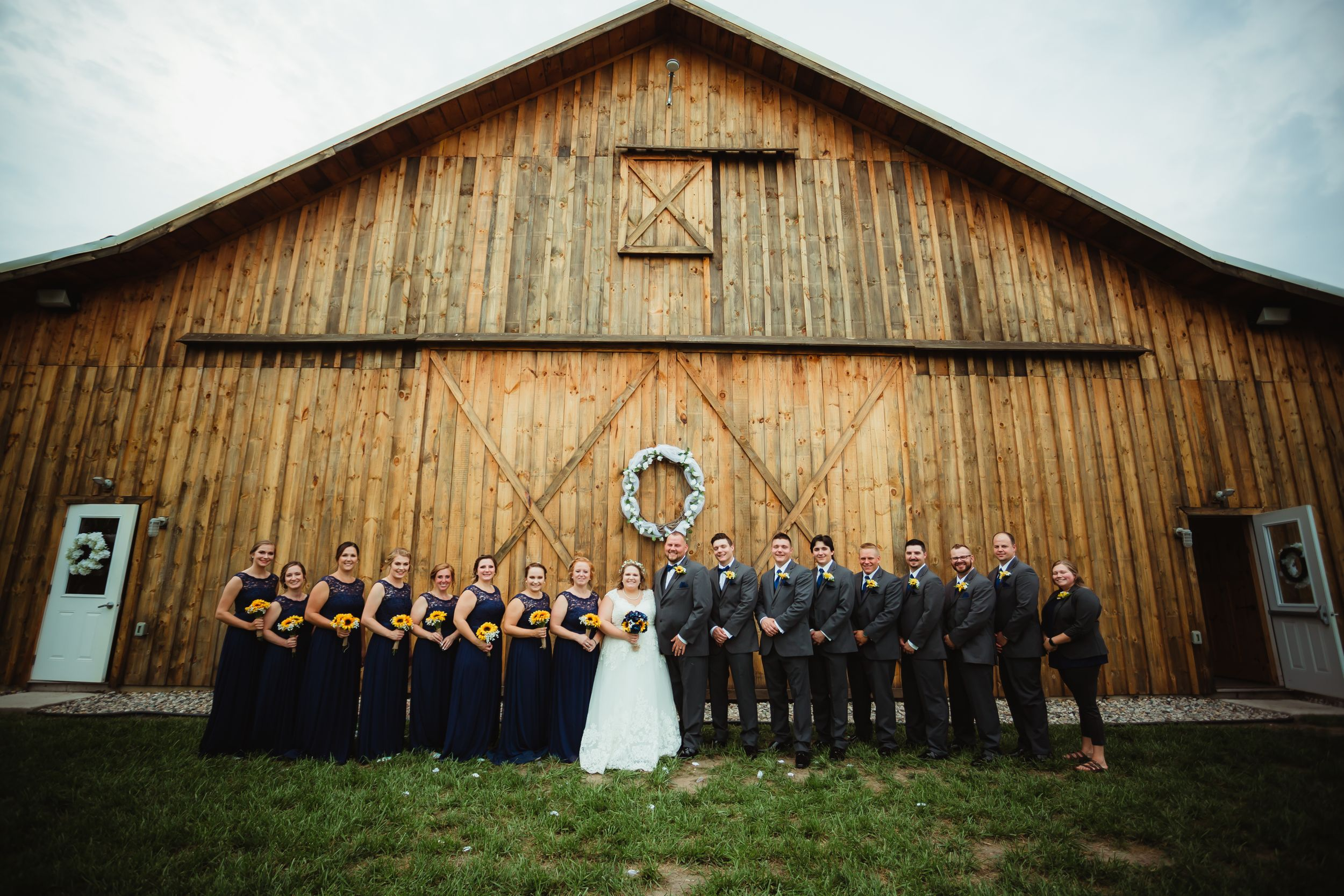 Wide photo of the wedding party smiling in a line in front of the barn.