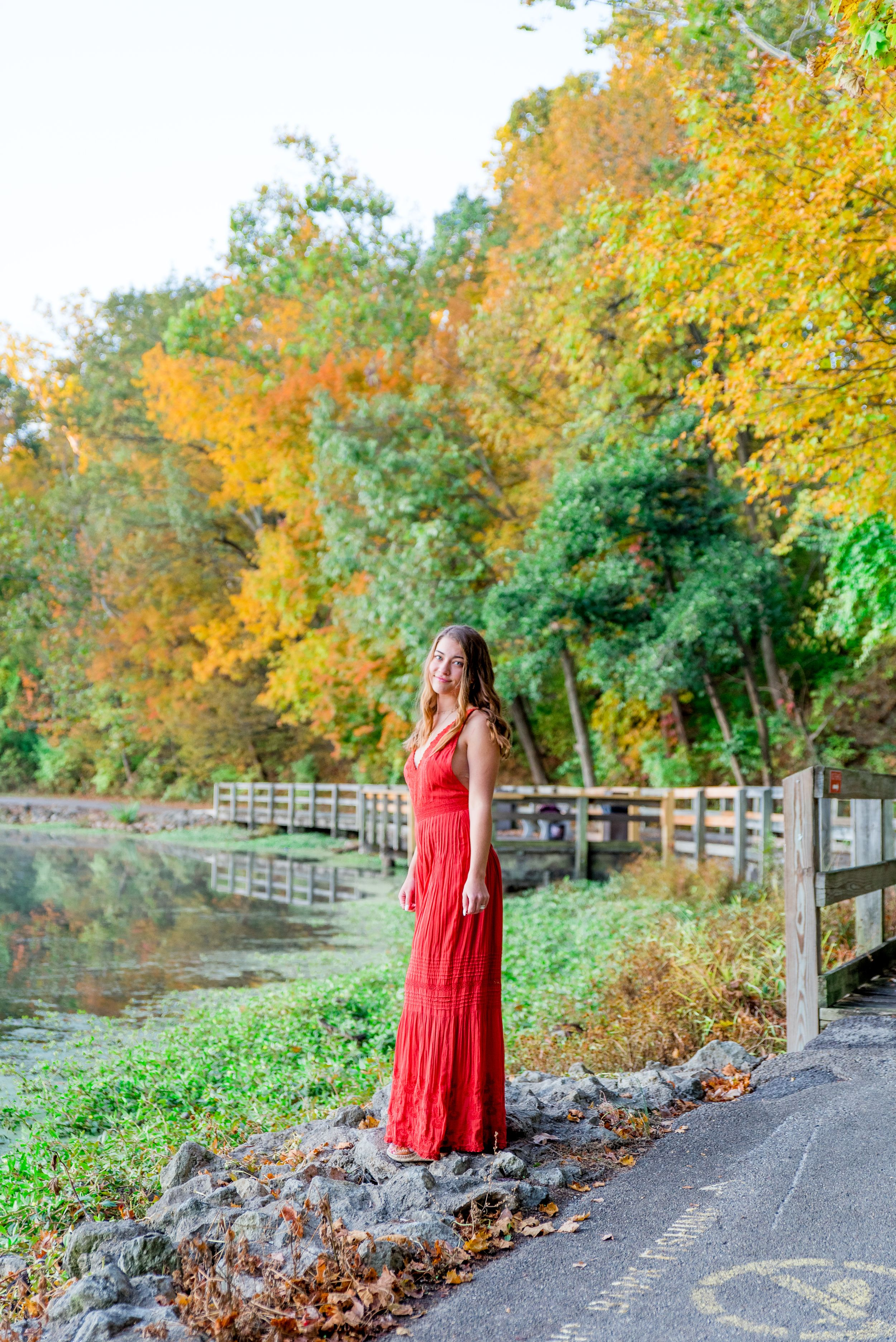 high schooler in orange jumpsuit standing on bridge in Chicago park for senior pictures in the fall