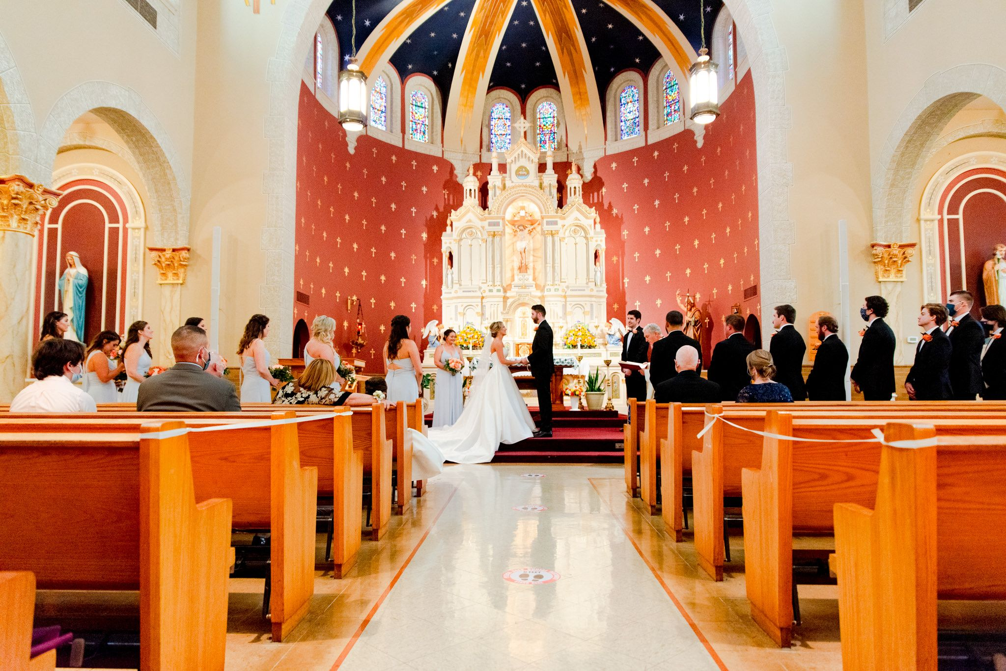 wide image of bride and groom at altar looking at each other and holding hands, showing wedding guests and the church