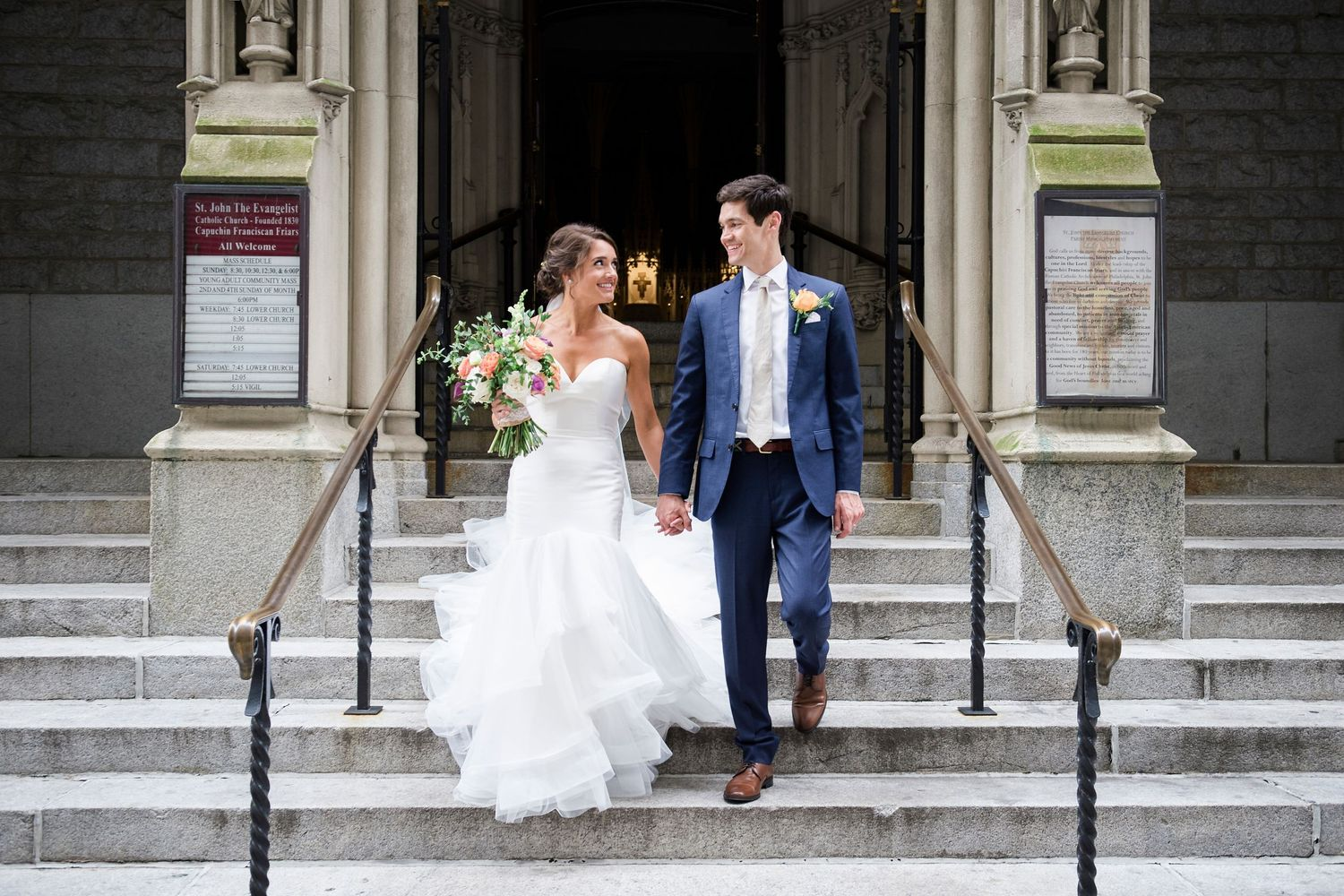 bride and groom exiting down stairs of philadelphia church wedding