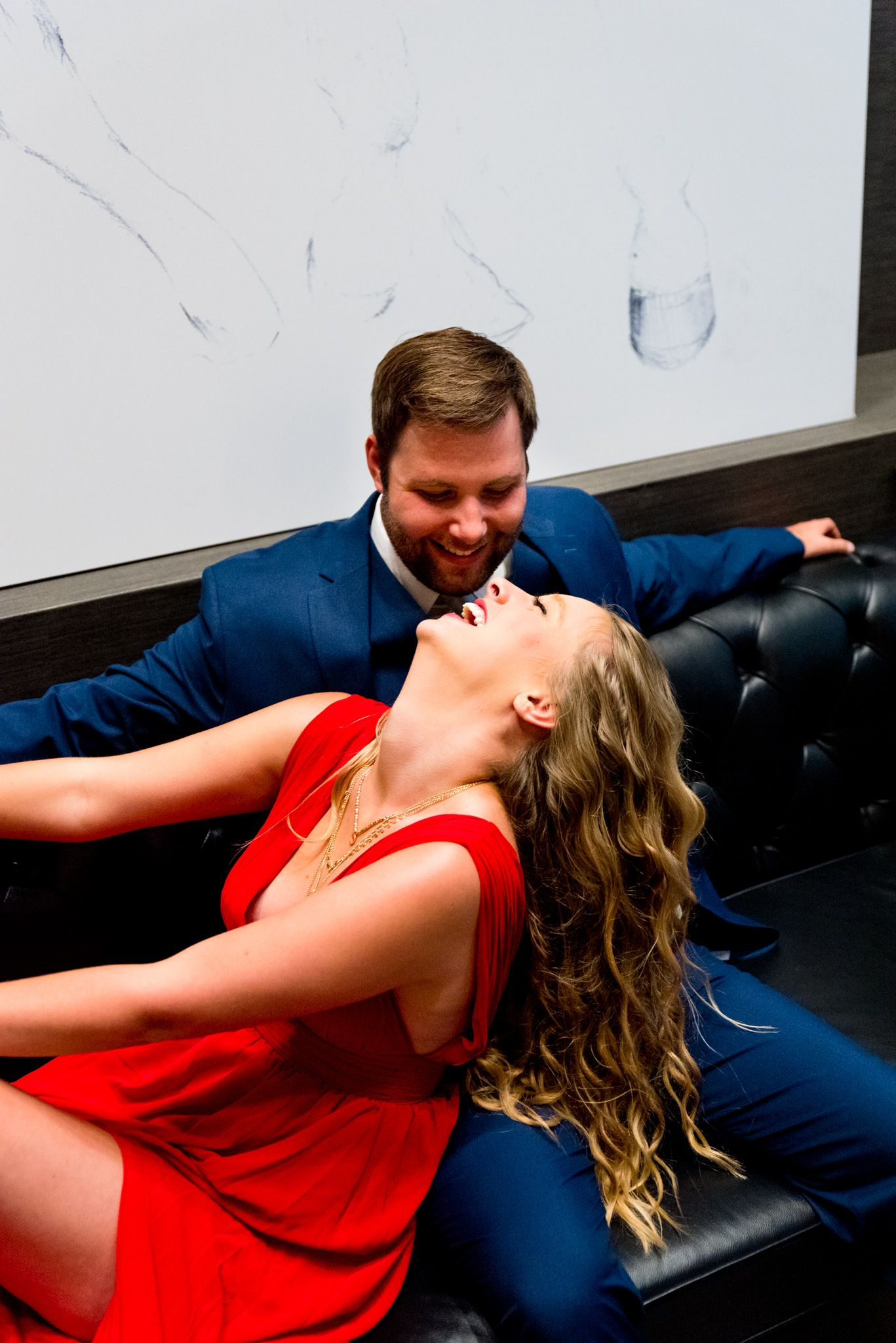 man in navy suit sitting on black leather couch and woman in red dress leans back and laughs