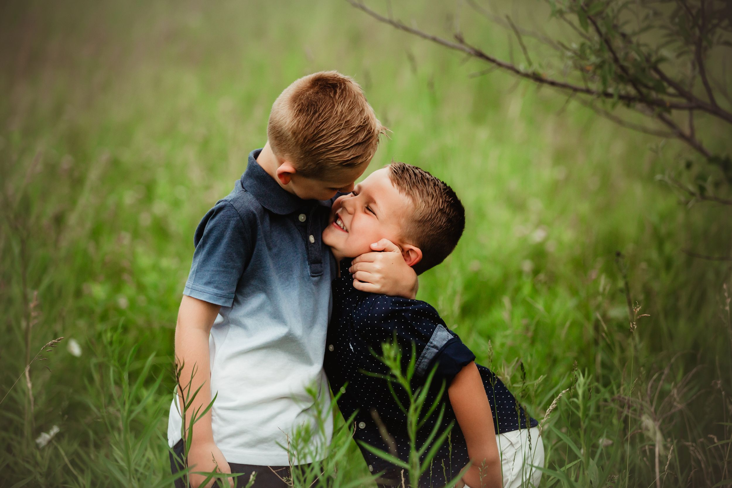 Photo of two young brothers smiling at each other and embracing.