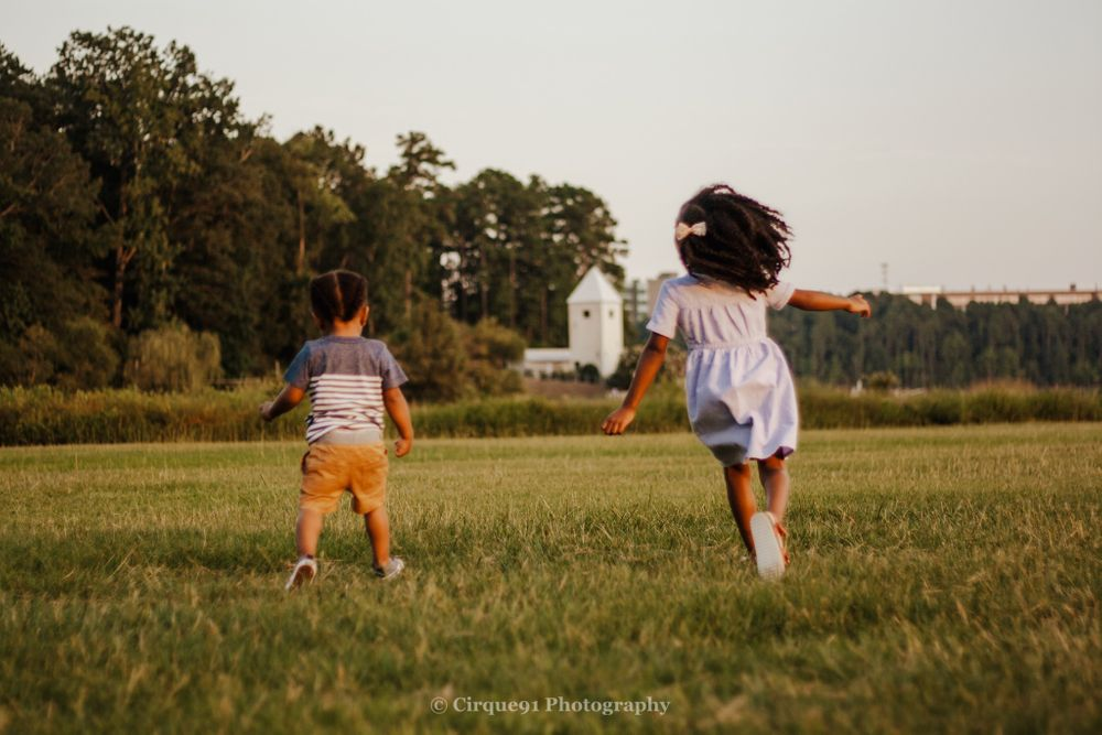brother and sistering chasing each other in the park in cary north carolina