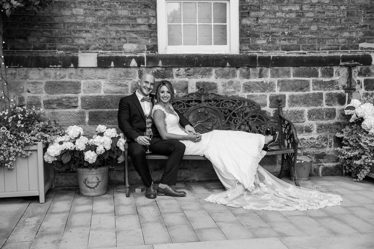 Bride & Groom sitting on bench at The West Mill Wedding Venue