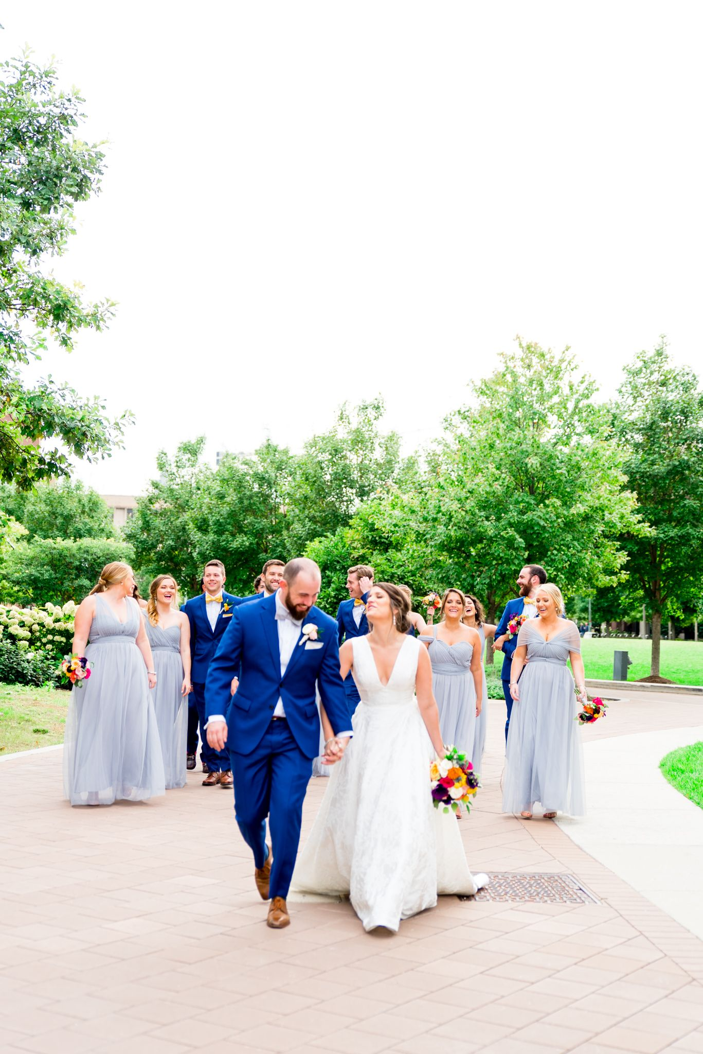 bride and groom walking with bridal party in light blue bridesmaid dresses and navy groomsmen suits at Loyola Chicago