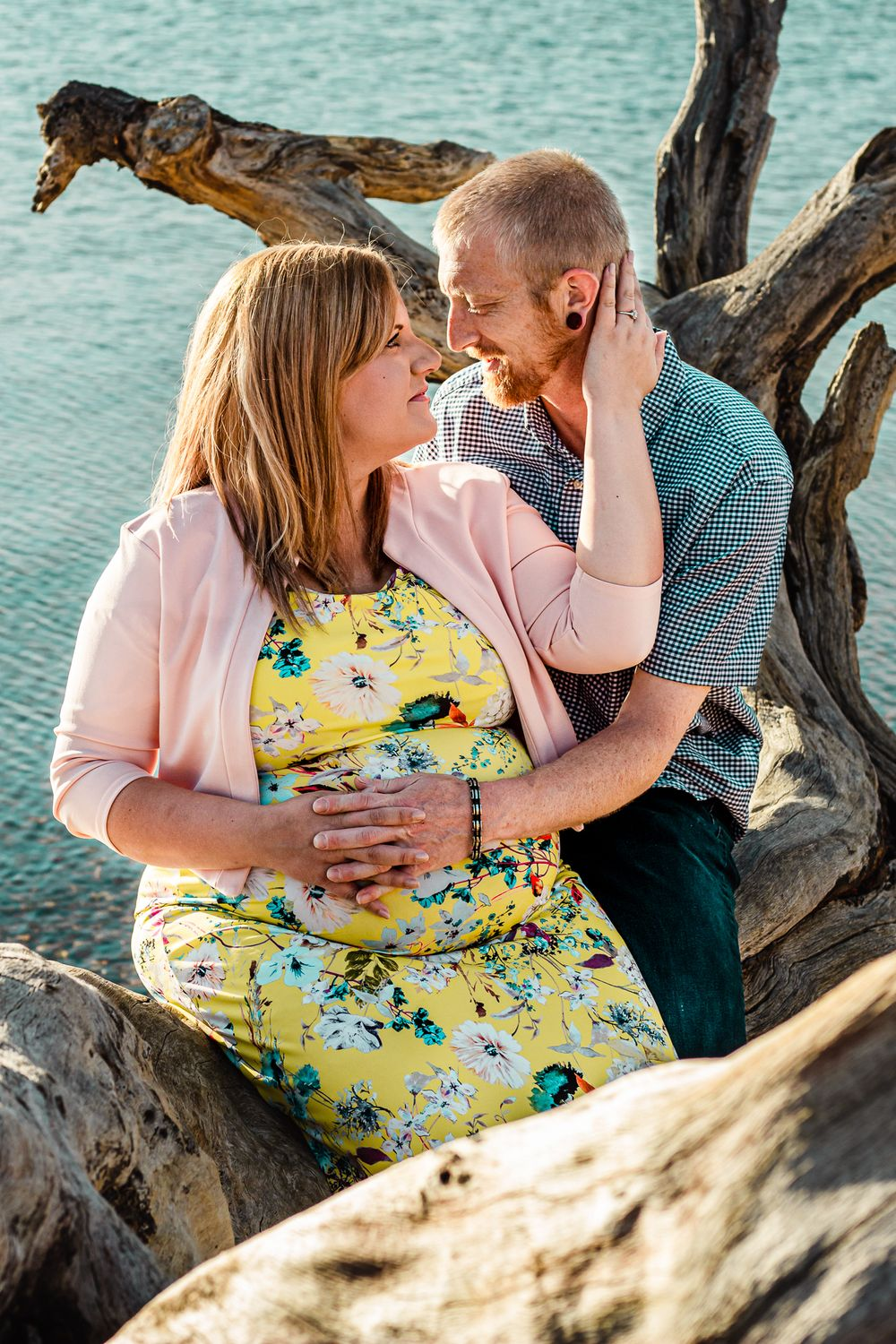 A maternity couple look at each other while sitting on a fallen tree on a beach on Hayling Island.
