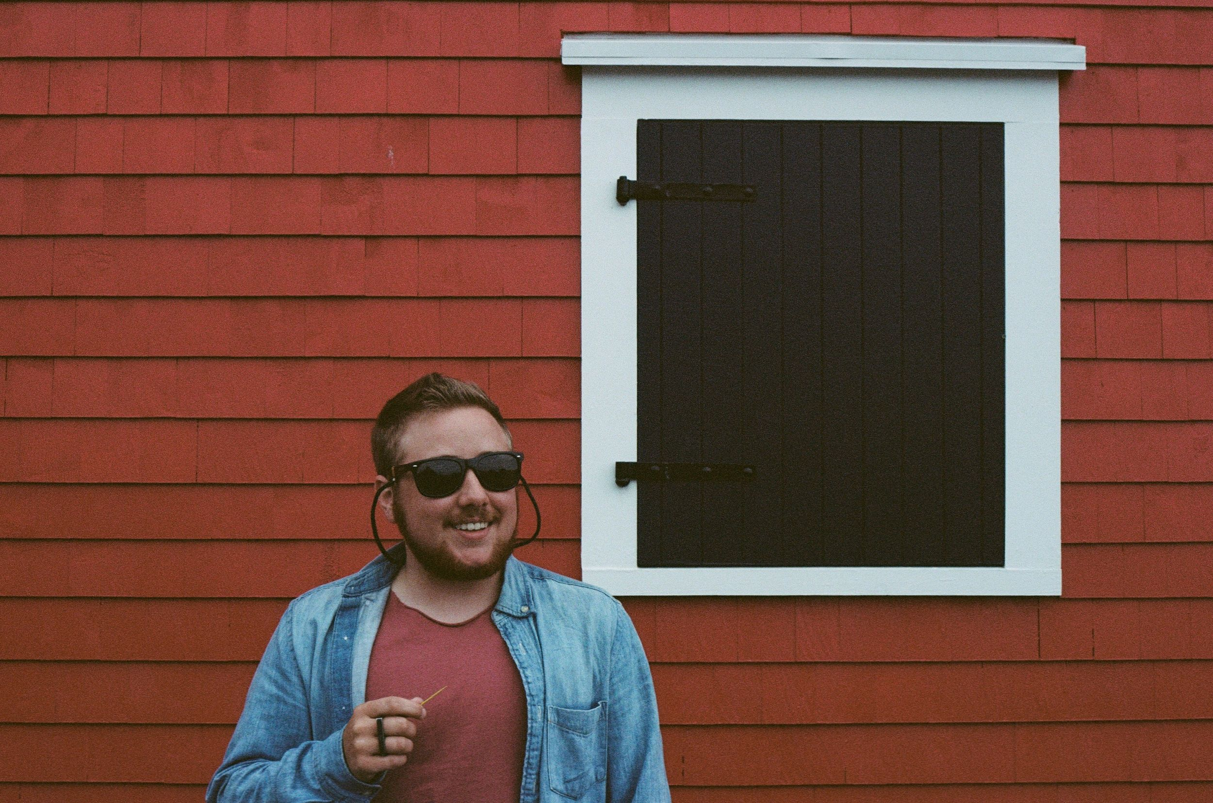 smiling man wearing blue denim shirt and sunglasses in front of red building 35mm film
