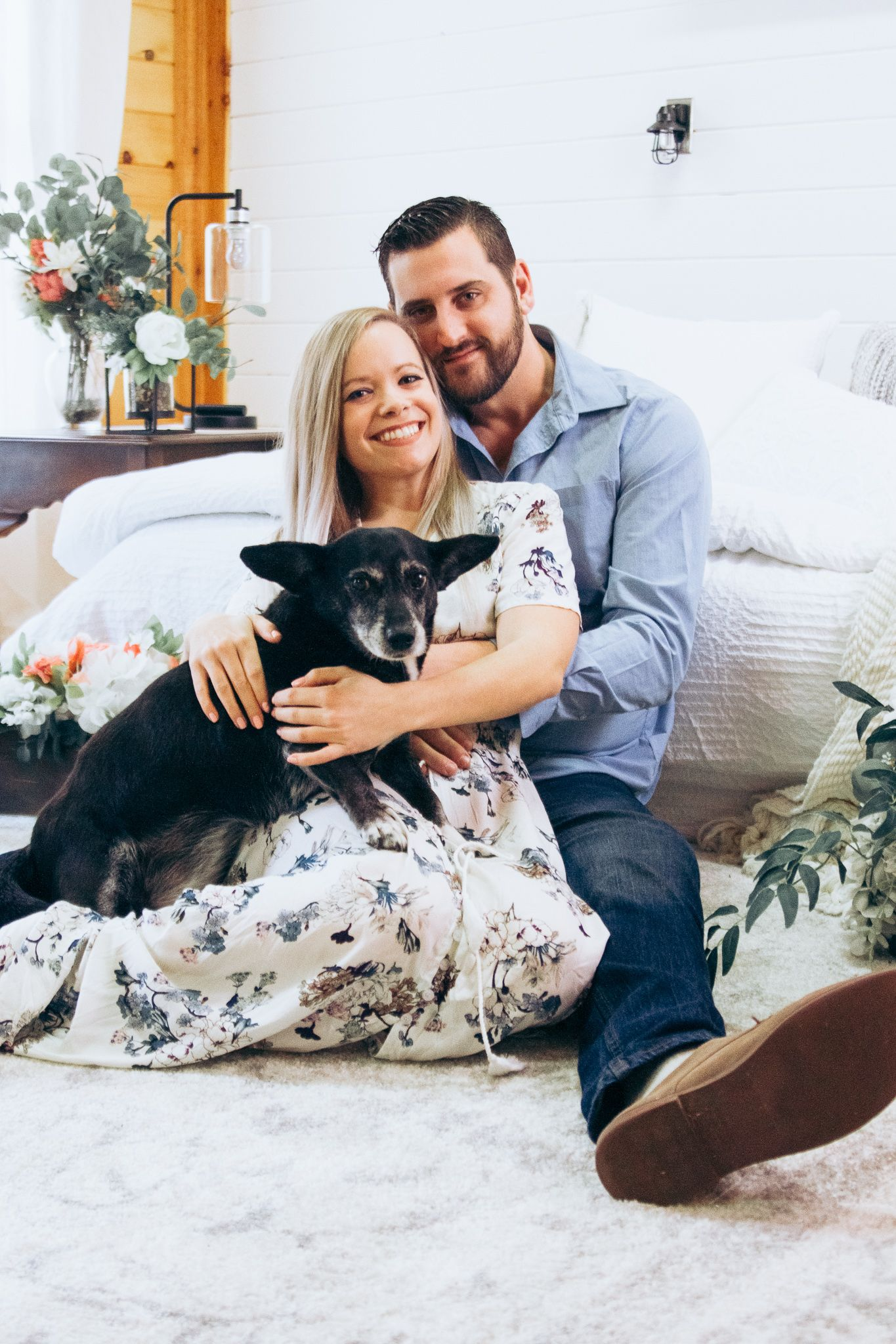 couple and dog sitting on carpeted floor smiling
