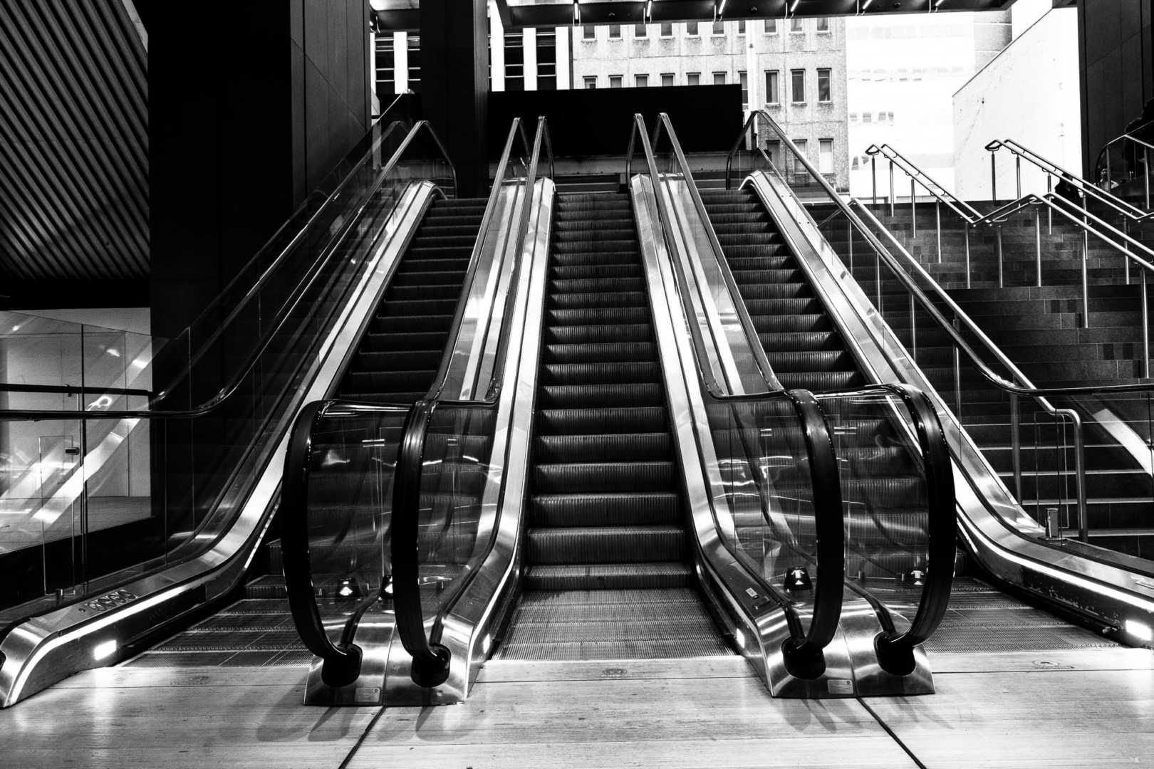 black and white image of an escalator