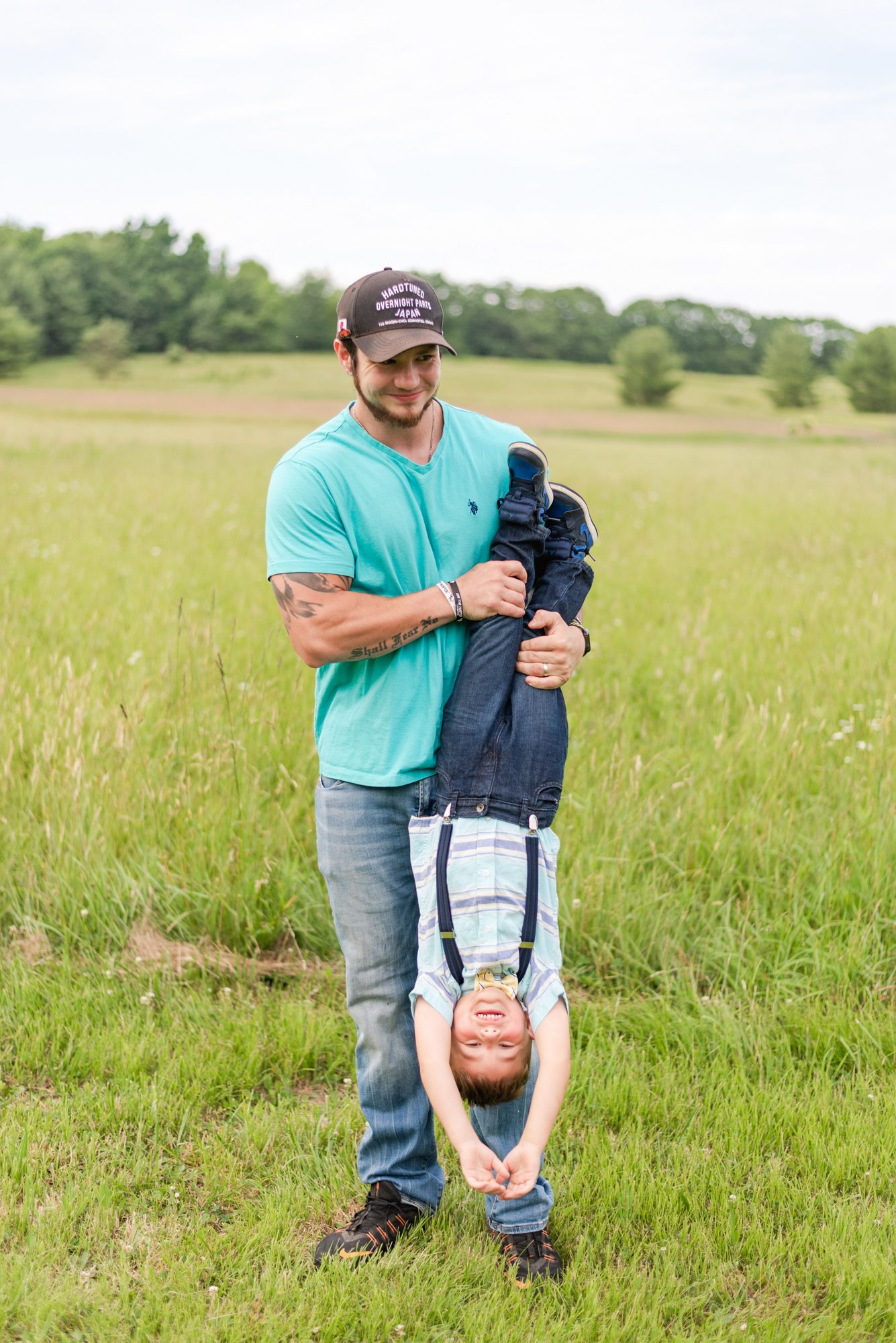 Dad holding boy upside down in field in Clarion Pennsylvania
