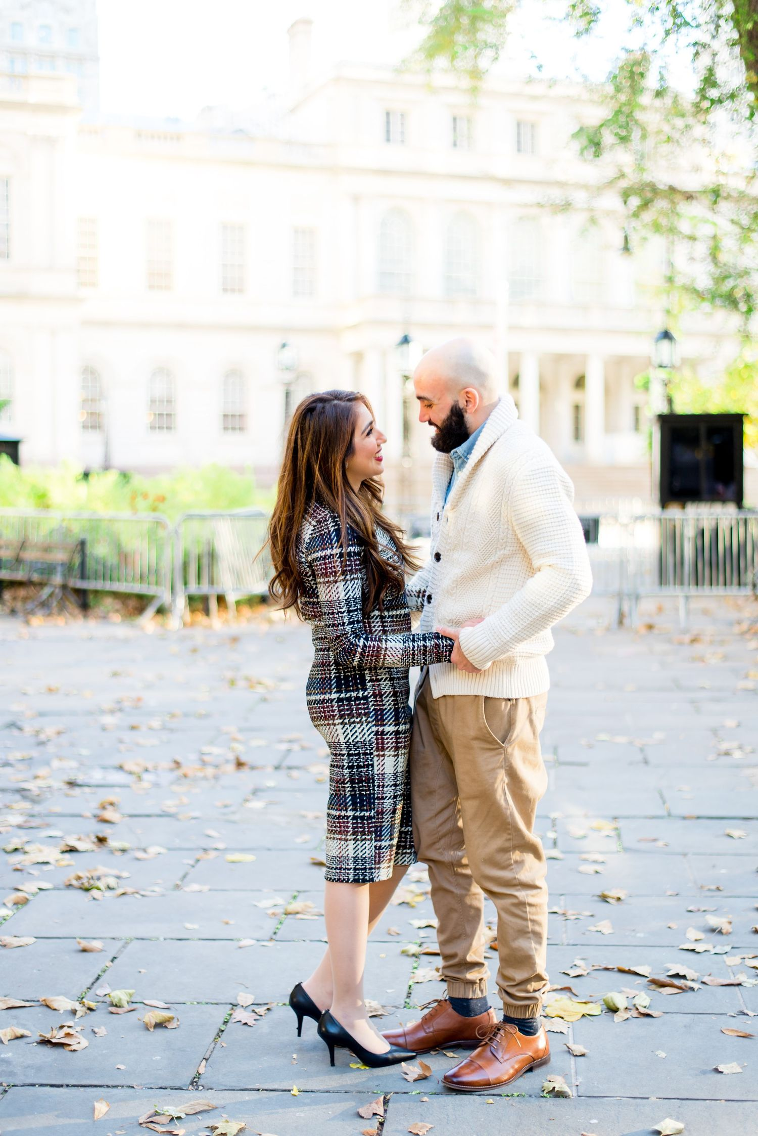 young engaged couple holding hands and smiling at each other at NYC City Hall for engagement pictures