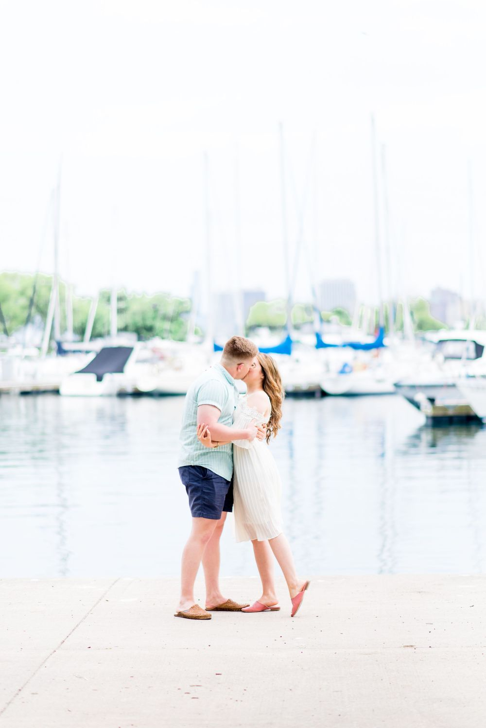 engaged couple hugging and kissing at Montrose Harbor in Chicago for sunrise engagement pictures