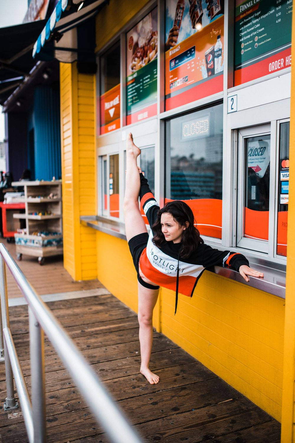 Girl dancing/doing the splits in front of a food booth at Santa Monica Pier