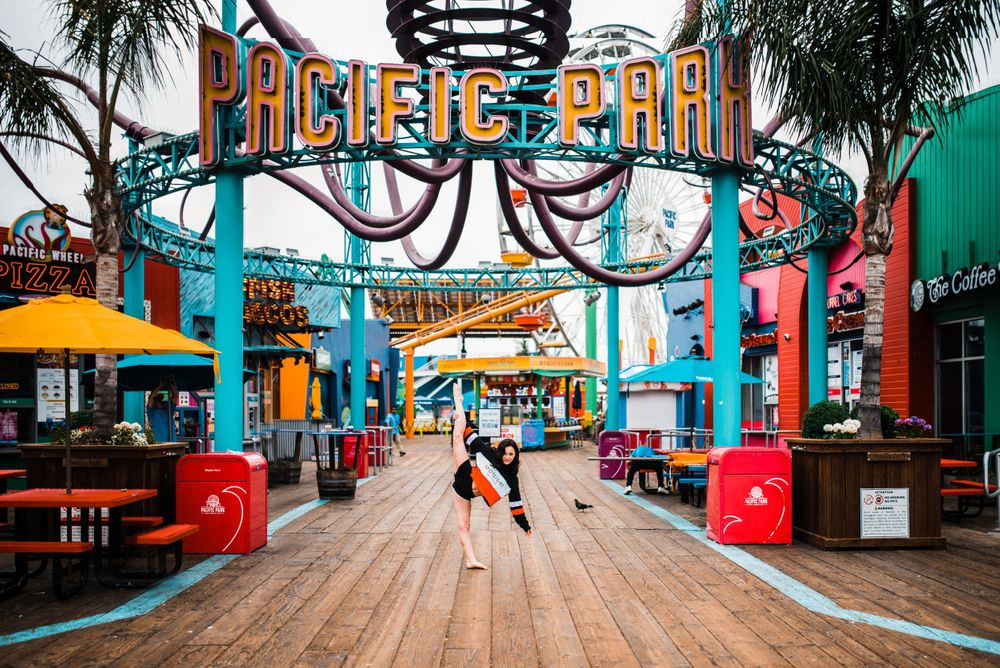 Girl dancing/doing the splits beneath the Pacific Pier sign at Santa Monica Pier. Colorful image.