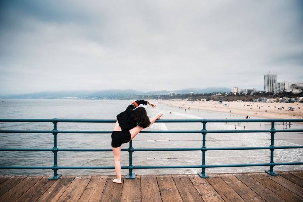 Girl stretching on the railing while overlooking the ocean and beach at Santa Monica Pier