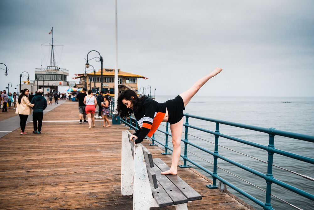 Girl dancing on a bench at Santa Monica Pier while strangers watch