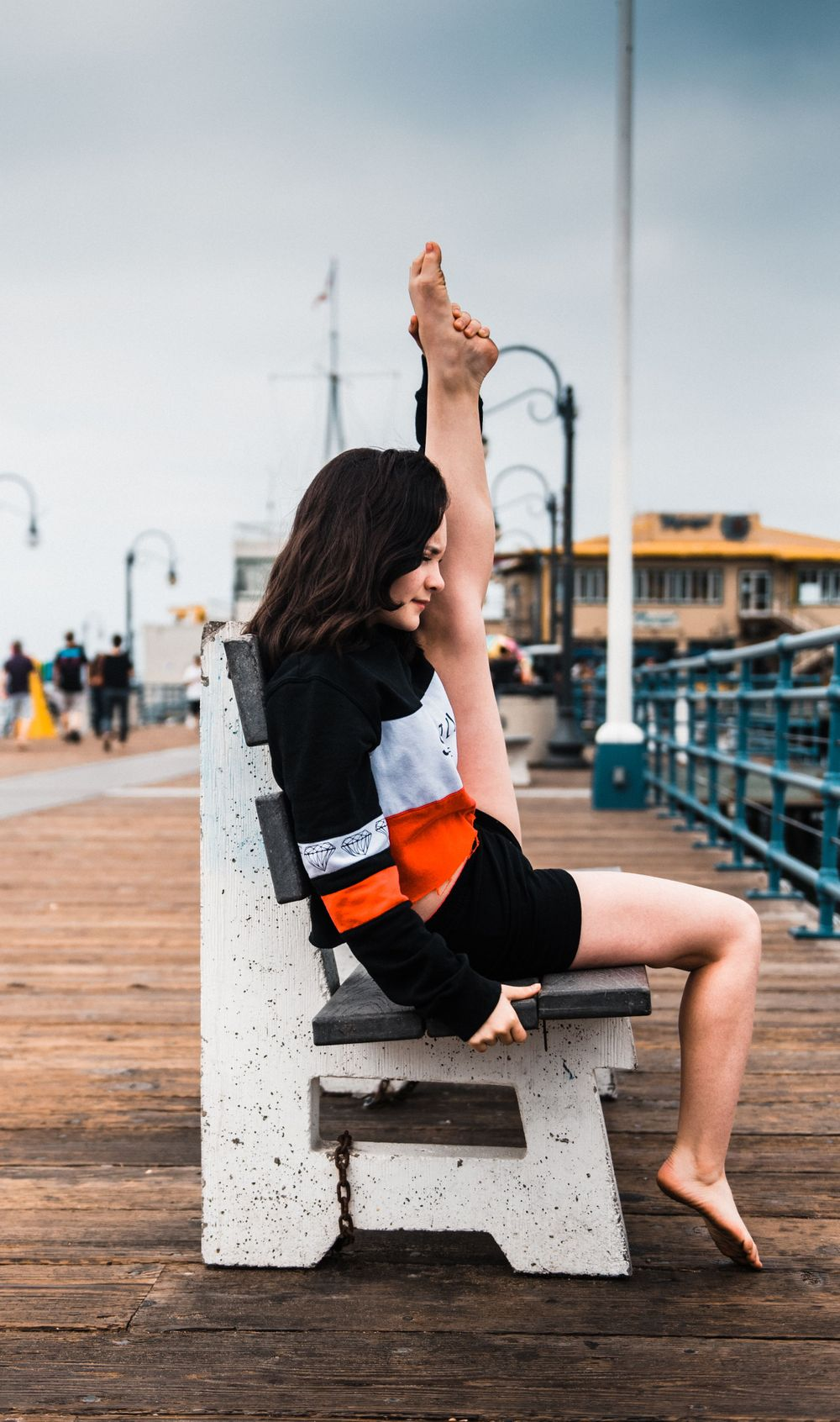Girl holding her leg up while dancing at Santa Monica Pier for a photoshoot