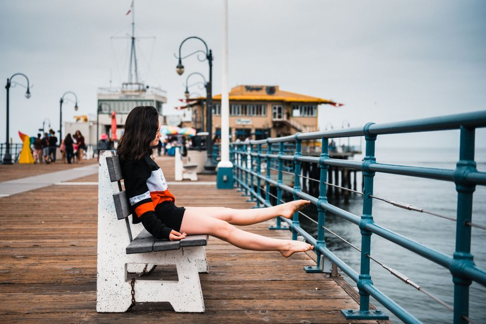 Girl pointing her toes while dancing for a photoshoot at Santa Monica Pier