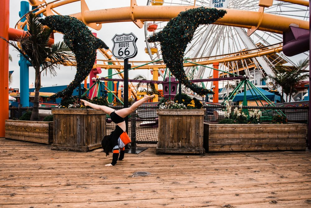 Girl doing a cartwheel while dancing in front of the rollercoaster at Santa Monica Pier