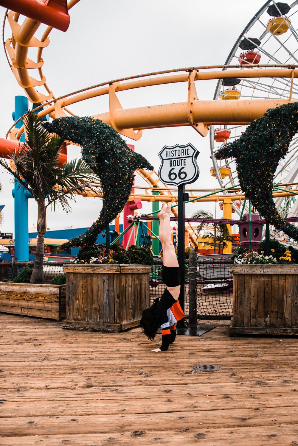 Girl doing a handstand while dancing in front of a rollercoaster during a Santa Monica Pier photoshoot