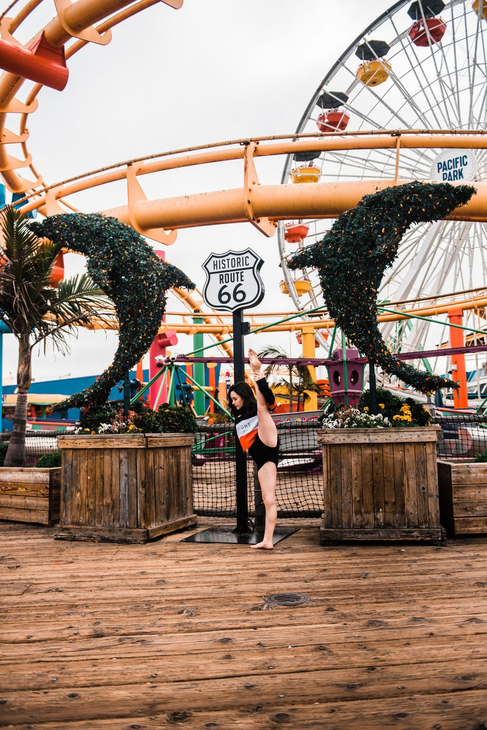 Girl doing the splits while dancing in front of a rollercoaster during a Santa Monica Pier photoshoot