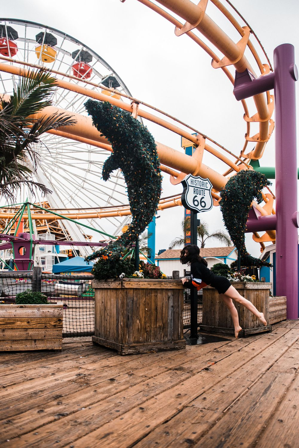 Girl dancing in front of a rollercoaster during a Santa Monica Pier photoshoot
