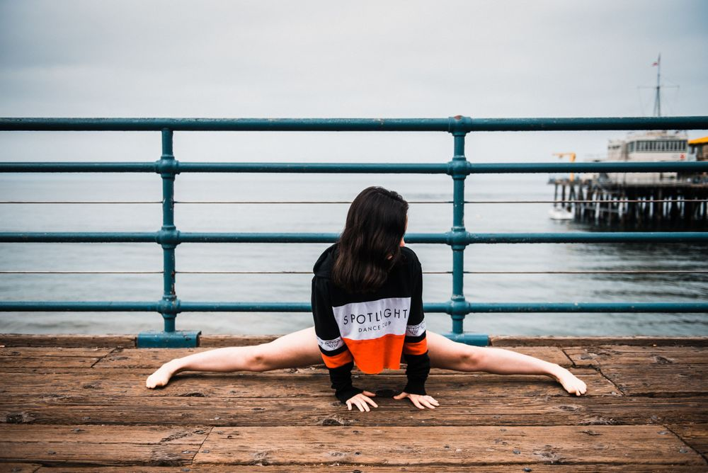 Girl doing the splits while dancing for a photoshoot at Santa Monica Pier