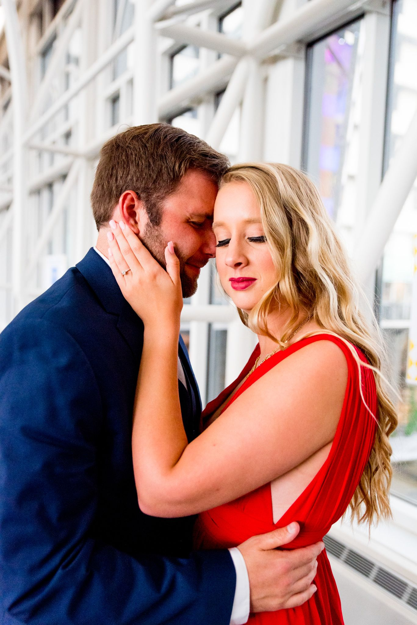 blonde woman in red dress looking at camera while fiance in navy suit rests on her forehead