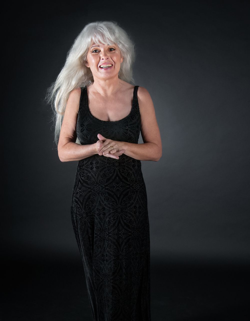 senior citizen with long silver hair stands for portrait