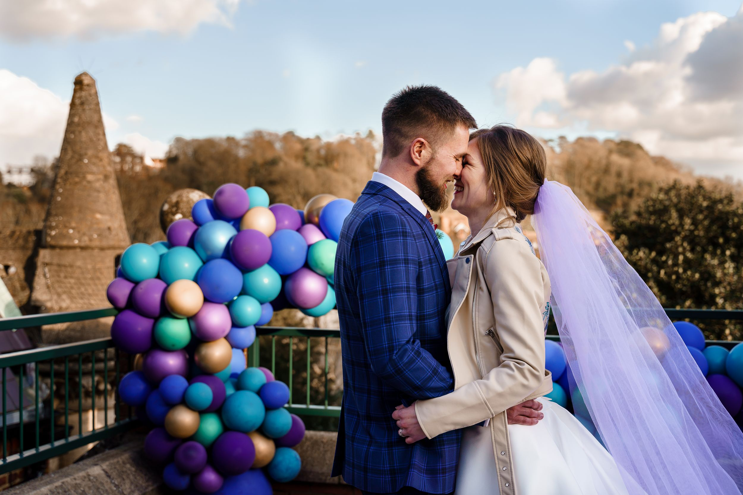 Colourful peacock wedding theme photography with balloons and a purple veil at Winchester Guildhall.