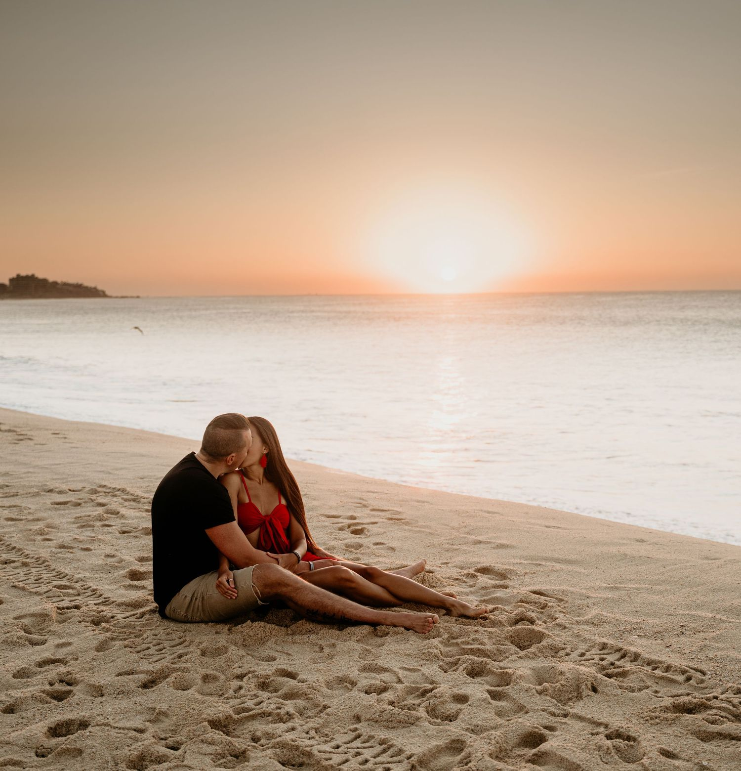 Husband and wife sitting on the beach during sunrise kissing.