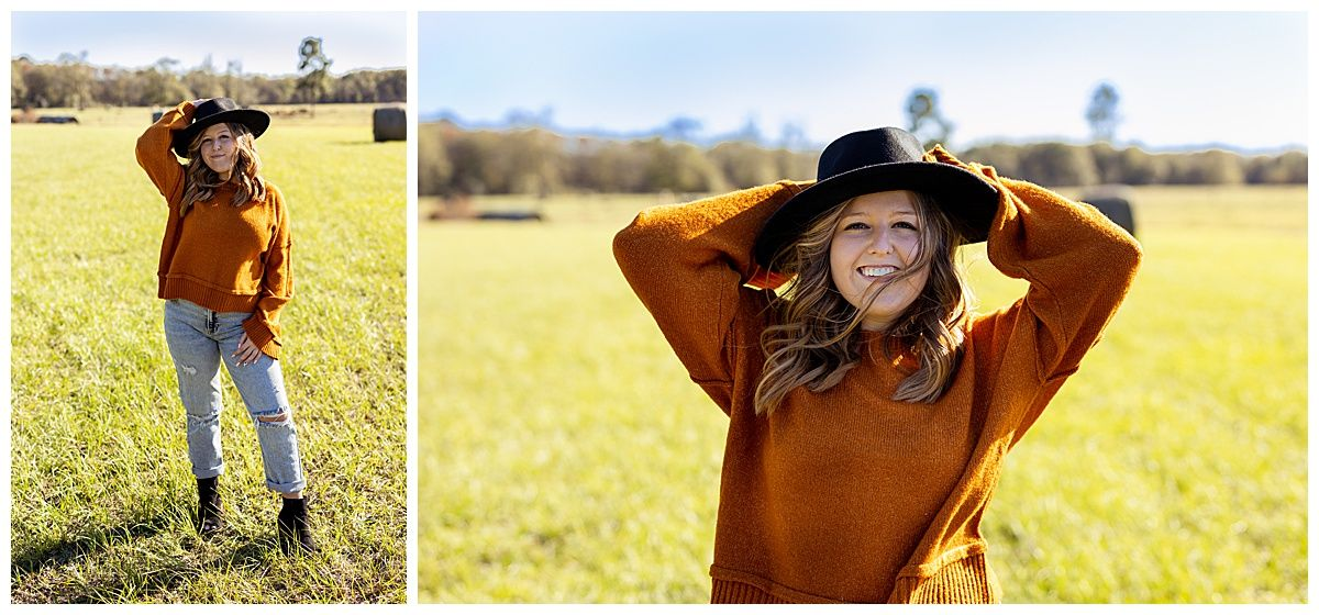 senior girl posing in a grassy field wearing a sweater and hat