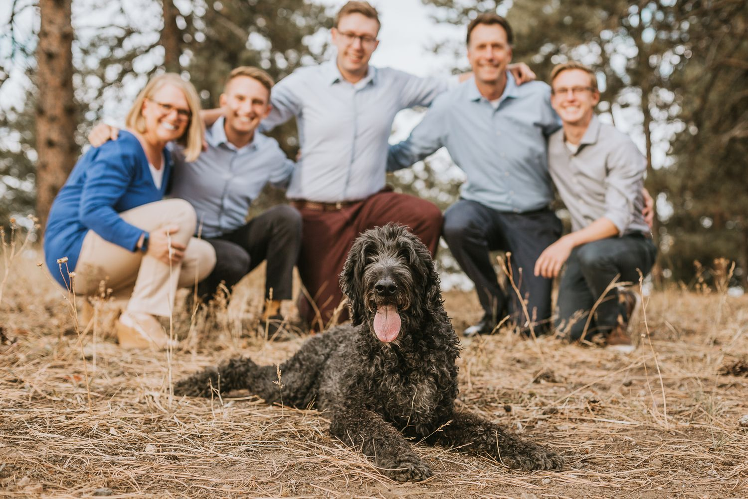 Family poses behind their dog during their Family Photography Session at Mount Falcon Trailhead in Morrison, Colorado.