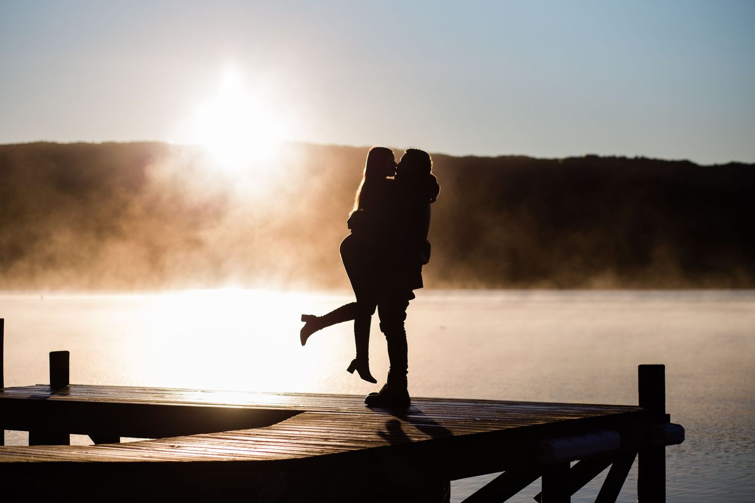 Newly engaged couple kissing with Taraera sunrise backdrop